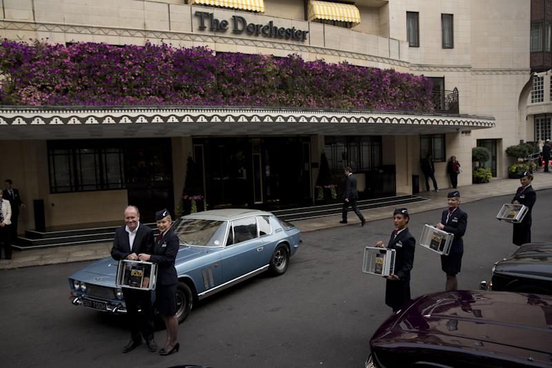 """William Boyd, left, the author of the new James Bond novel """"Solo"""" poses for photographers with flight attendants during a launch photocall outside the Dorchester Hotel in London, Wednesday, Sept. 25, 2013. """"Solo"""" is set in 1969 and takes the suave British spy, 45 years old and feeling his age, from London's plush Dorchester Hotel to a war-torn West African country and to Washington. (AP Photo/Matt Dunham)"""