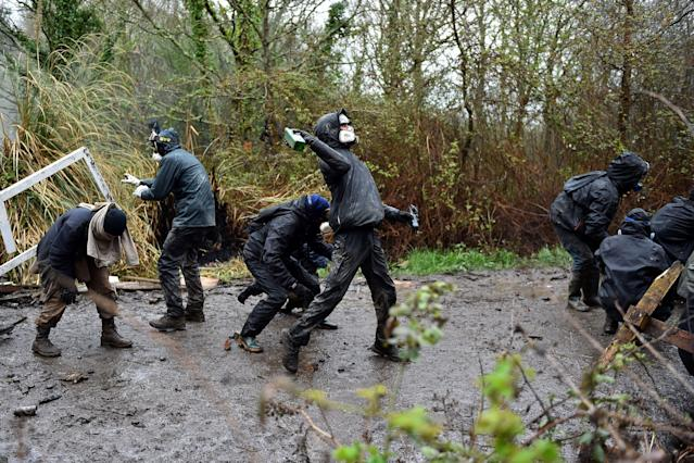 <p>A protester throws glass bottles at riot gendarme as clashes erupt on April 10, 2018 during a police operation to raze the decade-old camp known as ZAD (Zone a Defendre – Zone to defend) at Notre-Dame-des-Landes, near the western city of Nantes, and evict the last of the protesters who had refused to leave despite the government agreeing to ditch a proposed airport.<br> (Photo: Loic Venance/AFP/Getty Images) </p>