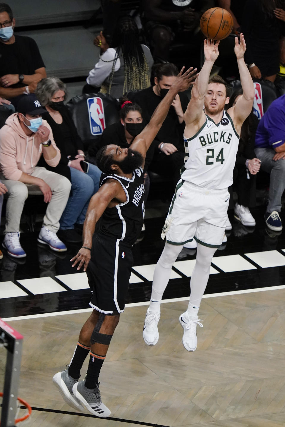 Milwaukee Bucks' Pat Connaughton, right, shoots over Brooklyn Nets' James Harden, left, during the second half of Game 7 of a second-round NBA basketball playoff series Saturday, June 19, 2021, in New York. (AP Photo/Frank Franklin II)