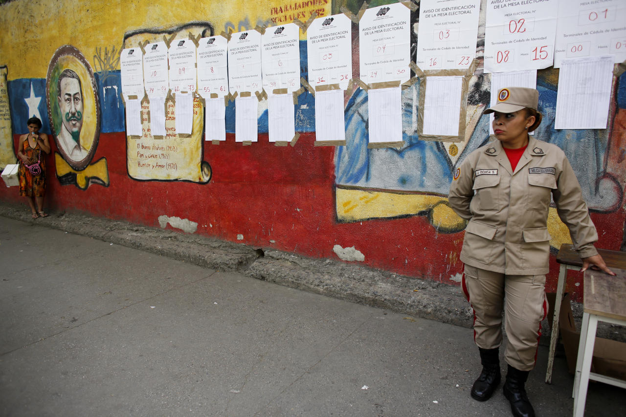 <p>A member of the Bolivarian Militia stands in front of voter lists at a polling station during the presidential election in Caracas, Venezuela, Sunday, May 20, 2018. Amidst hyperinflation and shortages of food and medicine, President Nicolas Maduro is seeking a second, six-year term in an election that a growing chorus of foreign governments refuse to recognize after key opponents were barred from running. (AP Photo/Ariana Cubillos) </p>