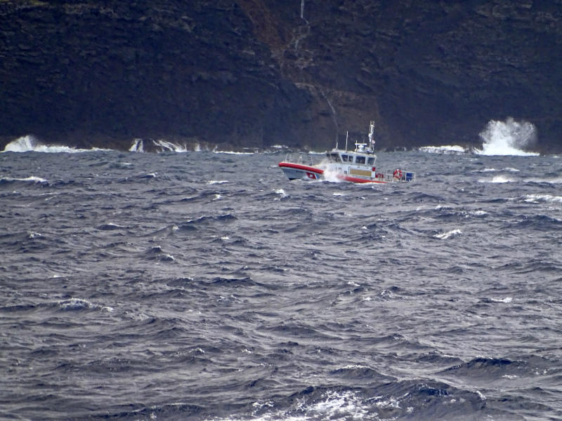 In this photo released by the U.S. Coast Guard, a coast guard vessel searches along the Na Pali Coast on the Hawaiian island of Kauai on Friday, Dec. 27, 2019, the day after a tour helicopter disappeared with seven people aboard. Authorities say wreckage of the helicopter has been found in a mountainous area on the island. (Lt. j.g. Daniel Winter/U.S. Coast Guard via AP)