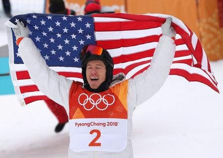 FILE PHOTO: Snowboarding - Pyeongchang 2018 Winter Olympics - Men's Halfpipe Finals - Phoenix Snow Park in Pyeongchang, South Korea - February 14, 2018 - Shaun White of the U.S. celebrates his win as he holds the U.S. flag. REUTERS/Issei Kato/File Photo