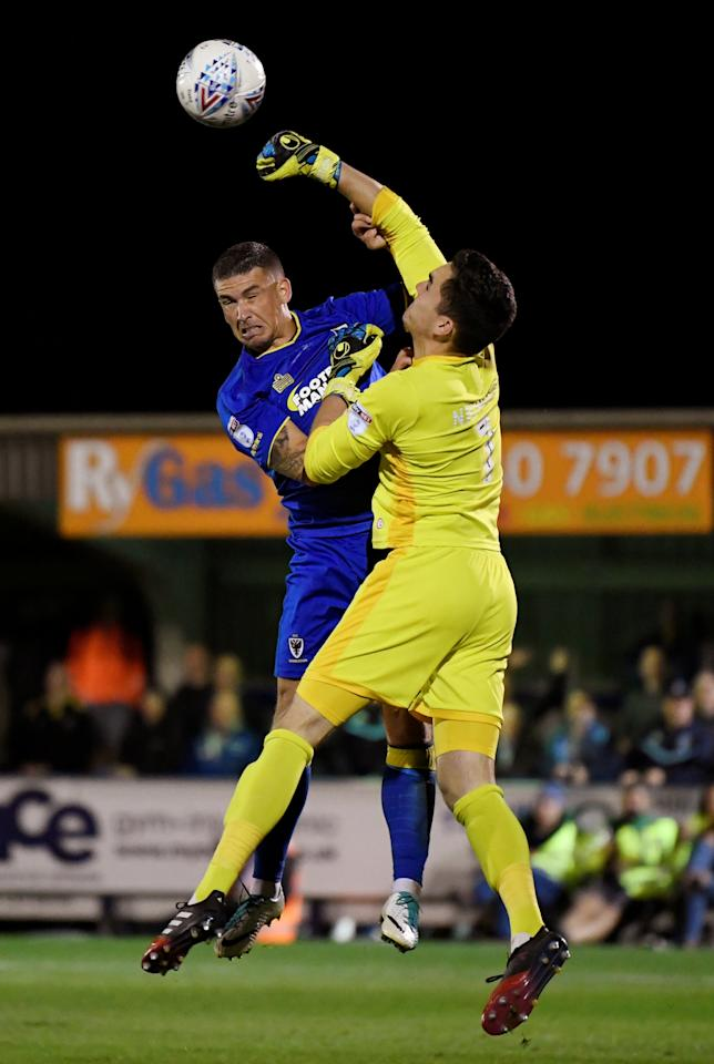 """Soccer Football - League One - AFC Wimbledon vs Milton Keynes Dons - Kingsmeadow, London, Britain - September 22, 2017  AFC Wimbledon's Cody Mcdonald in action with MK Dons' Lee Nicholls   Action Images/Tony O'Brien  EDITORIAL USE ONLY. No use with unauthorized audio, video, data, fixture lists, club/league logos or """"live"""" services. Online in-match use limited to 75 images, no video emulation. No use in betting, games or single club/league/player publications. Please contact your account representative for further details."""