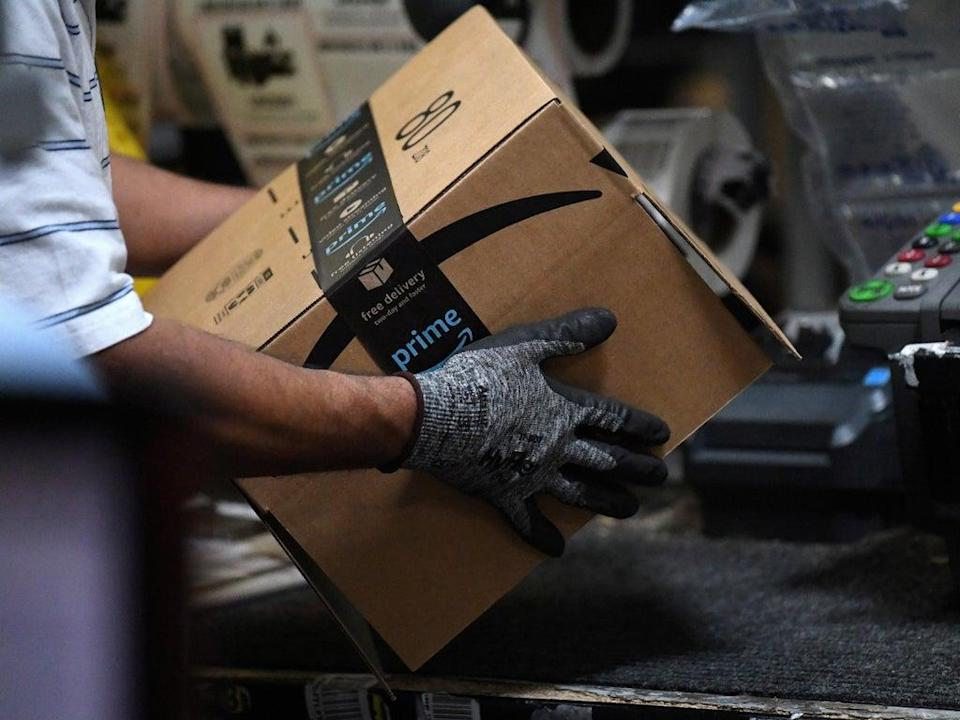 Worker assembles a box for delivery at an Amazon warehouse (Clodagh Kilcoyne/REUTERS)