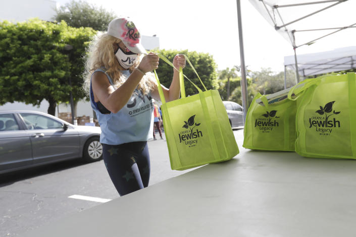 Volunteer Rachel Friedland prepares to load food in a car at a kosher food drive-thru distribution site, Wednesday, July 29, 2020, at the Greater Miami Jewish Federation building in Miami. (AP Photo/Wilfredo Lee)