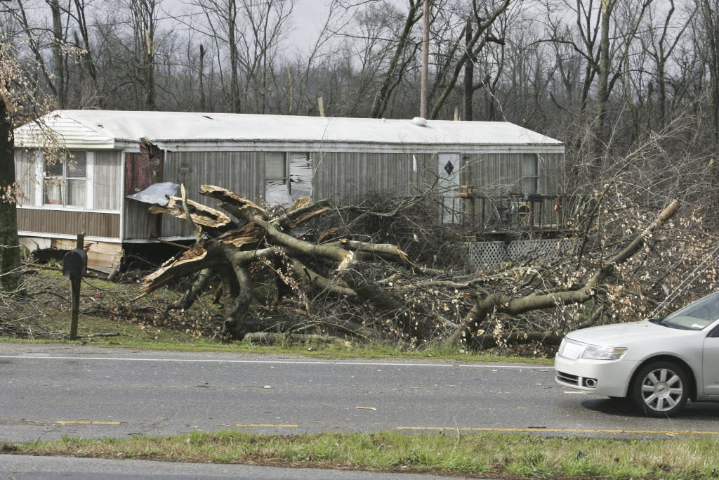 A tree falls in front of a mobile home after severe weather passed through on US Highway 72 West in Athens, Ala.  Friday March 2, 2012 A reported tornado destroyed several houses in northern Alabama as storms threatened more twisters across the region Friday. (AP Photo/The Huntsville Times, Robin Conn)