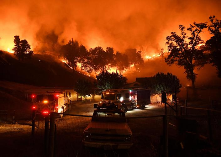Firefighters conduct a controlled burn to defend houses against flames from the Ranch fire: Getty
