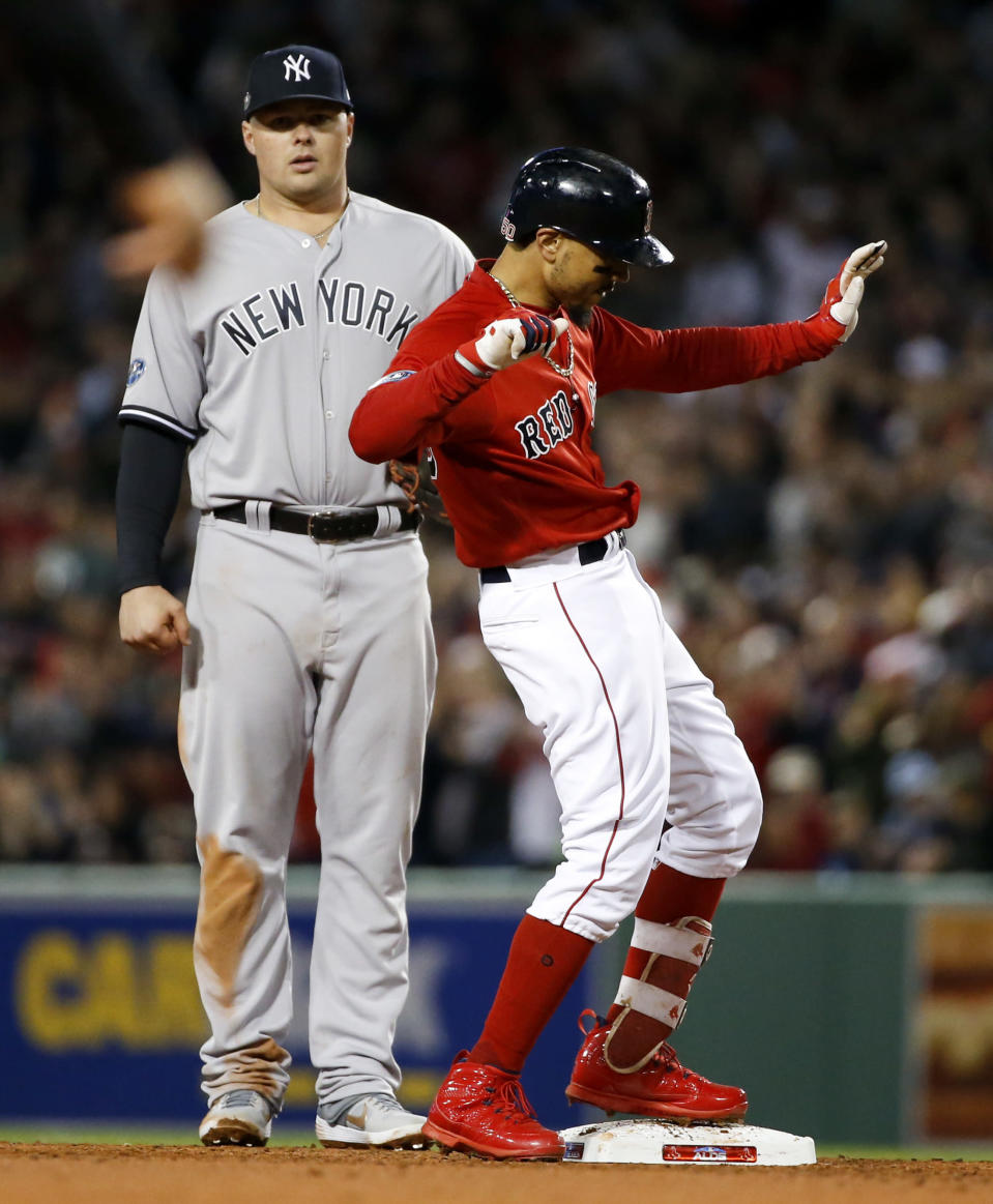 Boston Red Sox's Mookie Betts, right, celebrates after a double against the New York Yankees during the third inning of Game 1 of a baseball American League Division Series on Friday, Oct. 5, 2018, in Boston. (AP Photo/Elise Amendola)