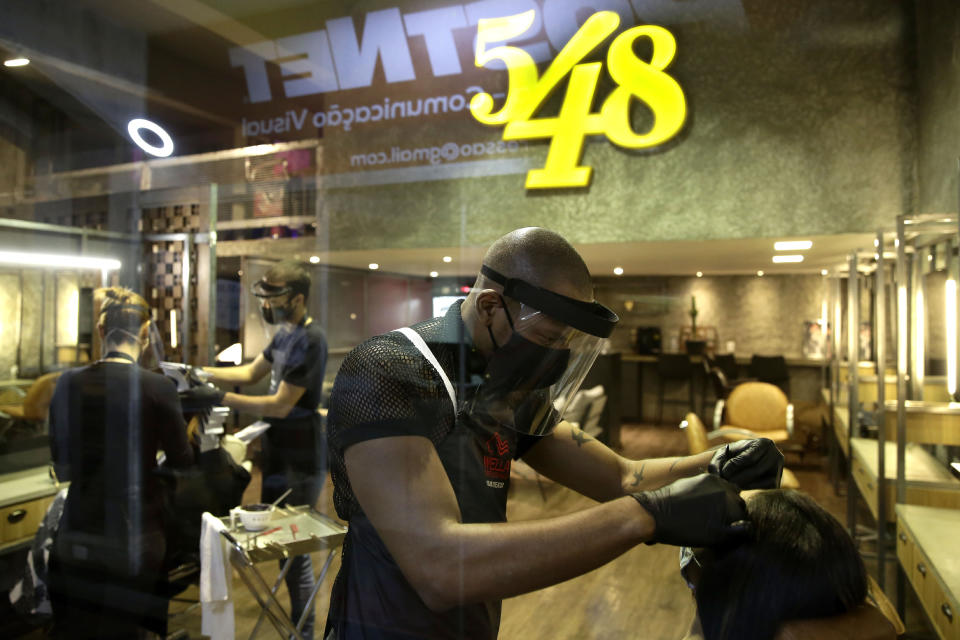 A hairdresser wears a face shield, mask, and gloves for protection amid the COVID-19 pandemic while attending a client on the first day the saloon was allowed to reopen, as restrictions ease in Brasilia, Brazil, Wednesday, July 15, 2020. (AP Photo/Eraldo Peres)