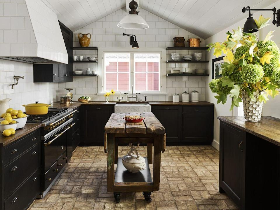 "<p>At this California ranch designed by Ken Fulk and Ike Kligerman Barkley, the guest house kitchen exudes beautiful rusticity with ceiling-height wall tiles in alternating dimensions (<a href=""https://www.waterworks.com/us_en/"" rel=""nofollow noopener"" target=""_blank"" data-ylk=""slk:Waterworks"" class=""link rapid-noclick-resp"">Waterworks</a>), reclaimed brick flooring, and oak countertops—all anchored by jet-black cabinets.</p><p><a class=""link rapid-noclick-resp"" href=""https://www.sherwin-williams.com/homeowners/color/find-and-explore-colors/paint-colors-by-family/SW6258-tricorn-black"" rel=""nofollow noopener"" target=""_blank"" data-ylk=""slk:Get the Look"">Get the Look</a></p>"