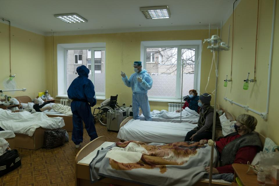 A medical worker talks with coronavirus patients in a hospital organized in the medical college in Lviv, Western Ukraine, on Monday, Jan. 4, 2021. A medical college in western Ukraine has been transformed into a temporary hospital as the coronavirus inundates the Eastern European country. The foyer of the college in the city of Lviv holds 50 beds for COVID-19 patients, and 300 more were placed in lecture halls and auditoriums to accommodate the overflow of people seeking care at a packed emergency hospital nearby. . (AP Photo/Evgeniy Maloletka)