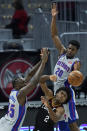 Cleveland Cavaliers' Collin Sexton, center, is stopped by Detroit Pistons' Sekou Doumbouya, left, and Josh Jackson in the second half of an NBA basketball game, Wednesday, Jan. 27, 2021, in Cleveland. The Cavaliers won 122-107. (AP Photo/Tony Dejak)