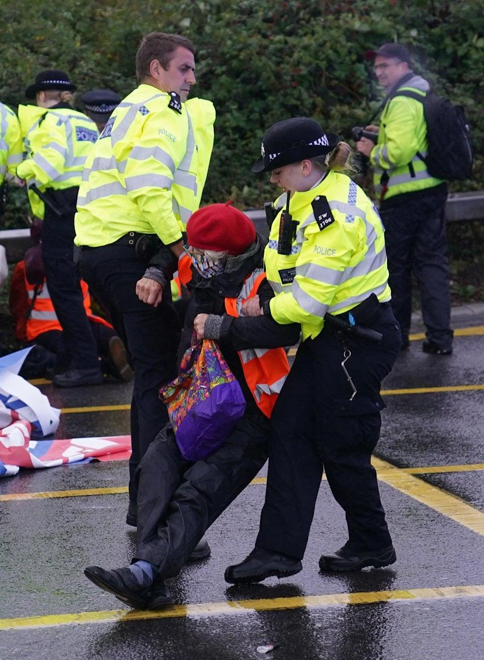 Police remove a protester from the roundabout leading from the M25 to Heathrow Airport (Steve Parsons/PA) (PA Wire)