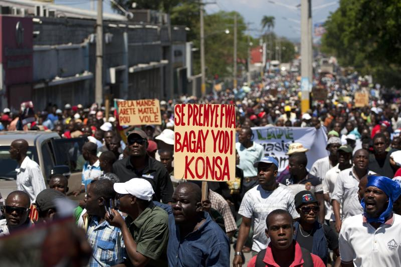 """A man marches with a banner that reads in Creole; """"It's the first time life is this hard,"""" during a demonstration marking the 27th anniversary of the signing of Haiti's Constitution, in Port-au-Prince, Haiti, Saturday, March 29, 2014. Those demonstrating called for the resignation of President Michel Martelly. The protesters say Martelly hasn't done enough to alleviate hunger since he was sworn in as president in May 2011. ( AP Photo/Dieu Nalio Chery)"""