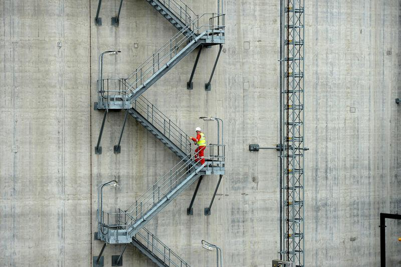 FILE PHOTO: Production manager Kevin Shears walks up a storage tank at National Grid's liquified natural gas plant at the Isle of Grain in southern England