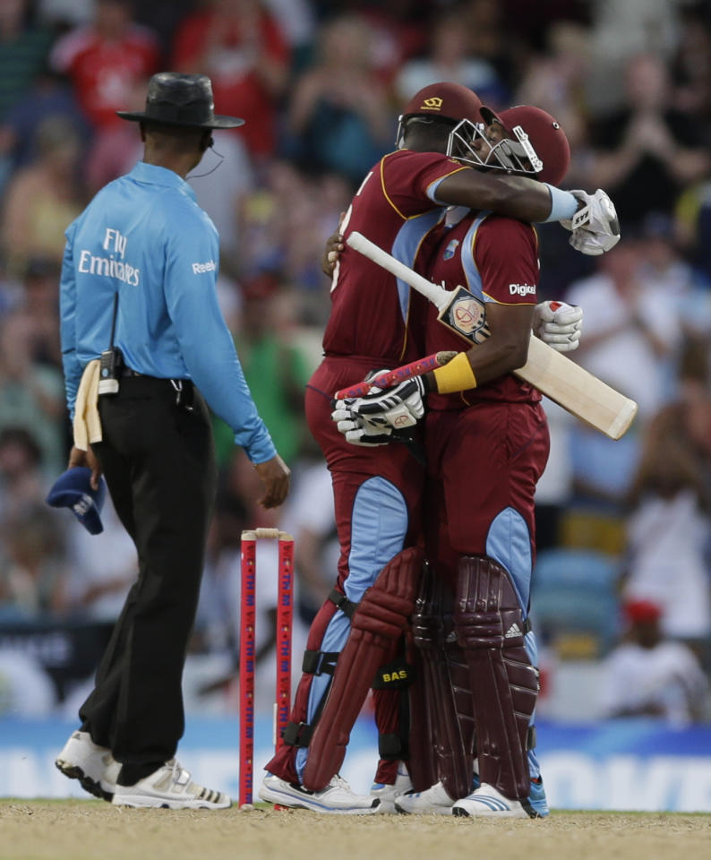 West Indies' Dwayne Bravo, right, and Darren Sammy embrace after beating England by 5 wickets with 7 balls remaining during their second T20 International cricket match at the Kensington Oval in Bridgetown, Barbados, Tuesday, March 11, 2014. (AP Photo/Ricardo Mazalan)
