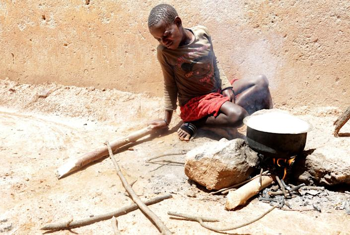 Twelve-year-old Sandra Gihozo cringes as smoke rises from a pot of beans, stoking the wooden fire beneath it in Mount Kigali village in Rwanda, on November 12, 2017. Her aunt Ruth Uwamahoro says Sandra's eyes and throat often hurt from the smoke, and that wood gathering sometimes makes her miss schoolwork. (Photograph by Yana Paskova)