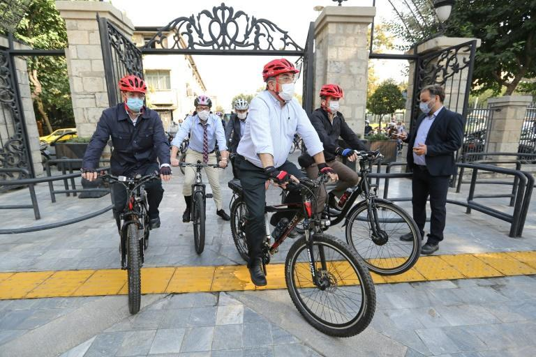 Tehran's mayor Pirouz Hanachi (C) and foreign diplomats ride bicycles through the Iranian capital to promote cycling on September 22