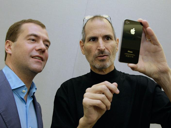 Russian President Dmitry Medvedev looks at an iPhone 4 with Apple CEO Steve Jobs.
