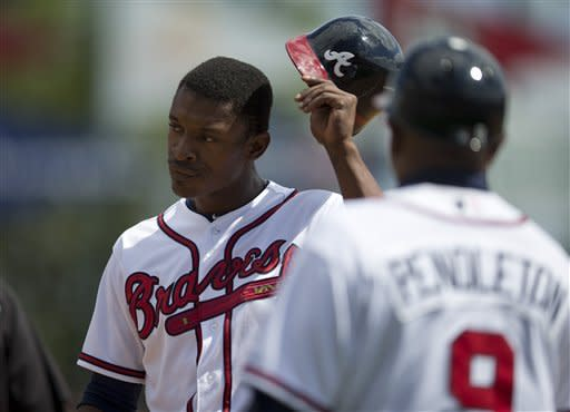 Atlanta Braves first base coach Terry Pendleton, right, looks on as B.J. Upton takes off his helmet after getting picked off first base during the fourth inning of an exhibition spring training baseball game against the Miami Marlins, Sunday, March 10, 2013, in Kissimmee, Fla. (AP Photo/Evan Vucci)