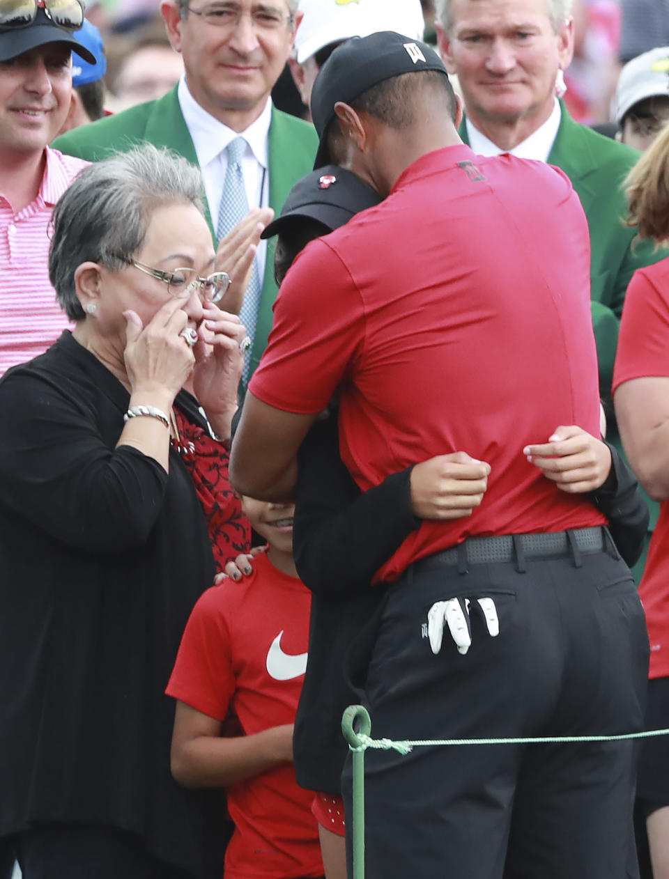 Tiger Woods mother Kultida Woods wipes away tears as he hugs his daughter Sam and son Charlie behind the 18th green after winning the Masters at Augusta National Golf Club on Sunday, April 14, 2019, in Augusta. Curtis Compton/ccompton@ajc.com