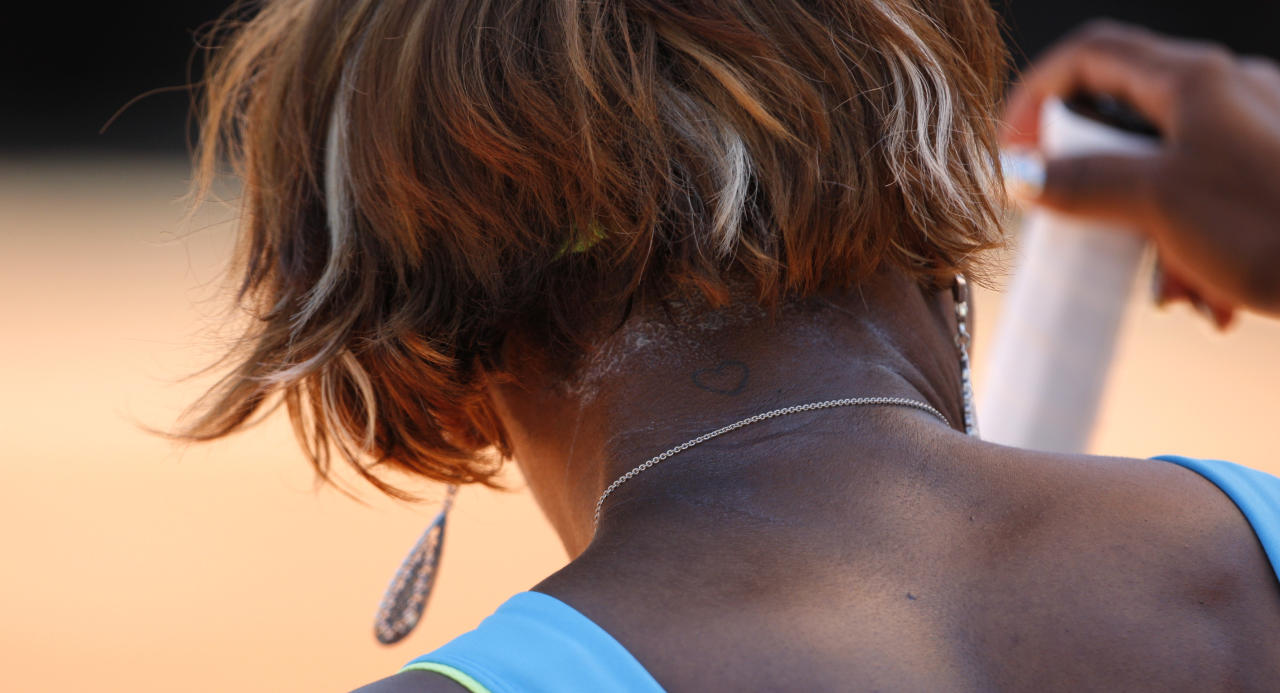 A small heart tattoo can be seen on the back of the neck of USA's Serena Williams as she takes a break during her first round match against Switzerland's Stefanie Voegele at the French Open tennis tournament at the Roland Garros stadium in Paris, Monday, May 24, 2010. (AP Photo/Christophe Ena)