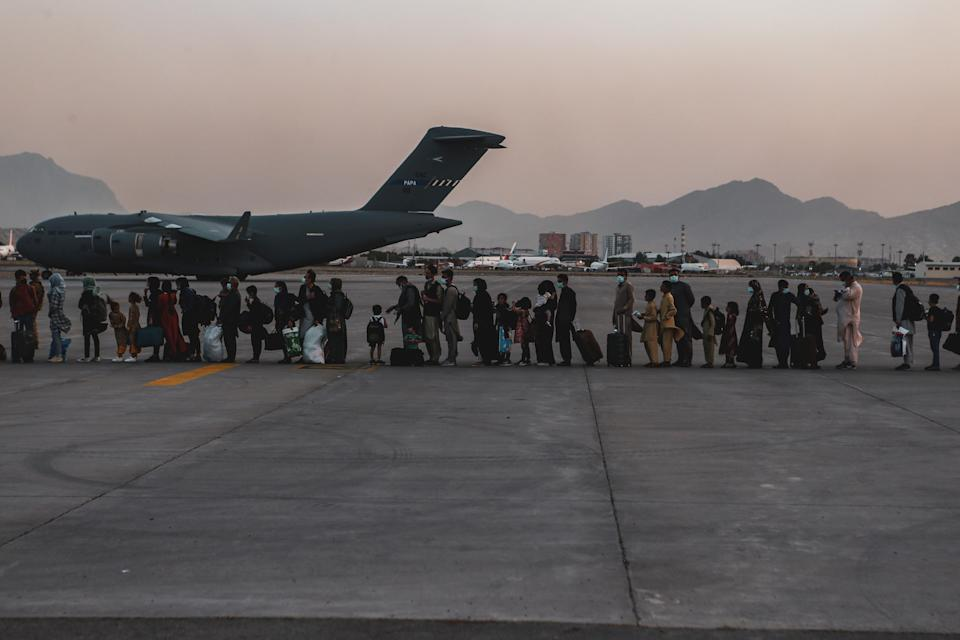 Evacuees wait to board a Boeing C-17 Globemaster III during an evacuation at Hamid Karzai International Airport in Kabul, Afghanistan, August 23, 2021. Picture taken August 23, 2021. U.S. Marine Corps/Sgt. Isaiah Campbell/Handout via REUTERS  THIS IMAGE HAS BEEN SUPPLIED BY A THIRD PARTY.