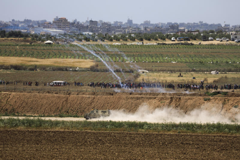 "Israeli troops fire tear gas at Palestinian protestord at he Israel and Gaza border fence, Wednesday, May 15, 2019. Palestinians are marking the 71st anniversary of their mass displacement during the 1948 war around Israel's creation. Demonstrations were held across the Israeli-occupied West Bank and the Gaza Strip on Wednesday to mark what the Palestinians call the ""nakba,"" or ""catastrophe."" (AP Photo/Tsafrir Abayov)"