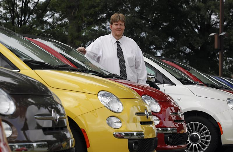 In this Tuesday, May 8, 2012, photo, James Tharp sales manger at Fiat of South Atlanta in Morrow, Ga., poses with new Fiats Tuesday May 8, 2012. Back when gas was cheap, Americans bought cars with V-8 engines like the Big Block, Cobra Jet and Ramcharger, but now, thanks to government regulation and gas-price gyrations, the motors that move the nation's cars and trucks are shrinking. (AP Photo/John Bazemore)
