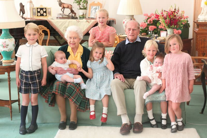 Britain's Queen Elizabeth and Prince Philip sit with Prince George, Prince Louis, Savannah Phillips, Princess Charlotte, Isla Phillips, Lena Tindall, and Mia Tindall