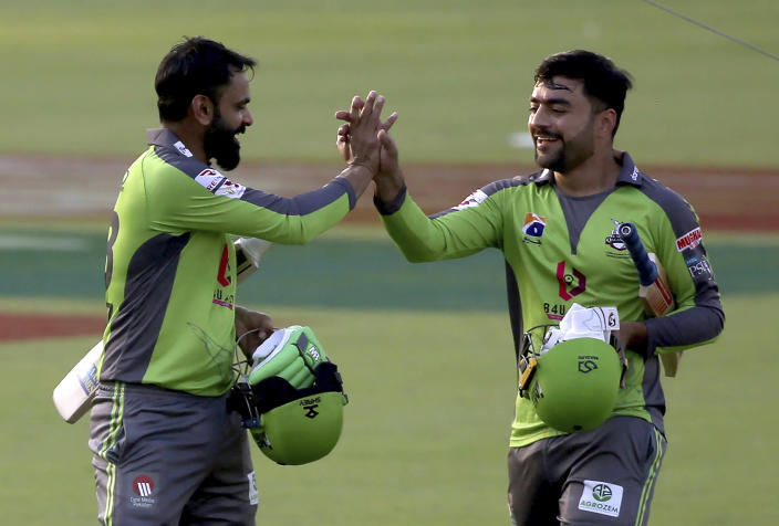 Lahore Qalandars Rashid Khan, right, and Mohammad Hafeez congratulate each other after taking winning run during a Pakistan Super League T20 cricket match between Peshawar Zalmi and Lahore Qalandars at the National Stadium, in Karachi, Pakistan, Sunday, Feb. 21 2021. (AP Photo/Fareed Khan)
