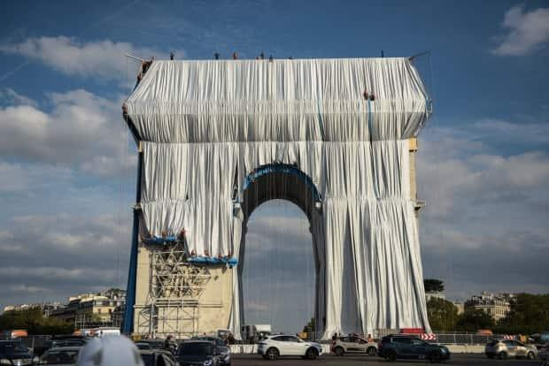 The fabric panels nearly cover the outer walls of the Arc de Triomphe in Paris.   (Benjamin Loyseau/Christo and Jeanne-Claude Foundation - image credit)