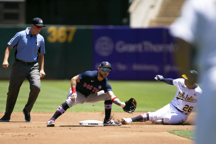 Oakland Athletics' Matt Chapman (26) slides safely into second base with a double ahead of the relay to Boston Red Sox second baseman Michael Chavis, center, during the first inning of a baseball game, Sunday, July 4, 2021, in Oakland, Calif. Umpire is Stu Scheurwater, left, looks on. (AP Photo/D. Ross Cameron)