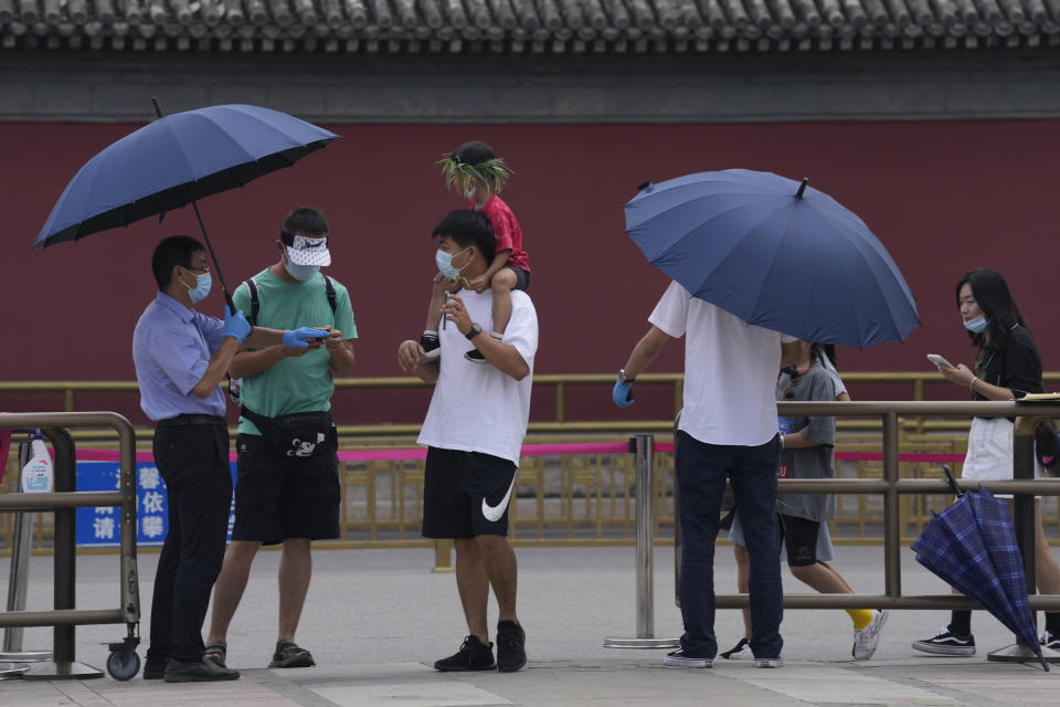 A worker checks the health code of tourists visiting the Summer Palace in Beijing on Aug. 3, 2021. Strict virus control measures have allowed China to return to relatively normal life. The number of tourists visiting Beijing in June and July tripled compared to the same period last year, while revenue quadrupled, according to Trip.com, China's largest online travel booking platform. (AP Photo/Ng Han Guan)