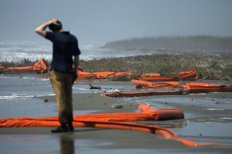 A television reporter stands beside oil booms at the coast of South Pass