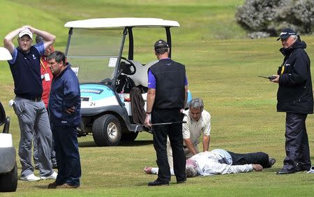 Caddie McGregor lies on the grass near his player Scotland's Forsyth during the Madeira Golf Open in Santo da Serra