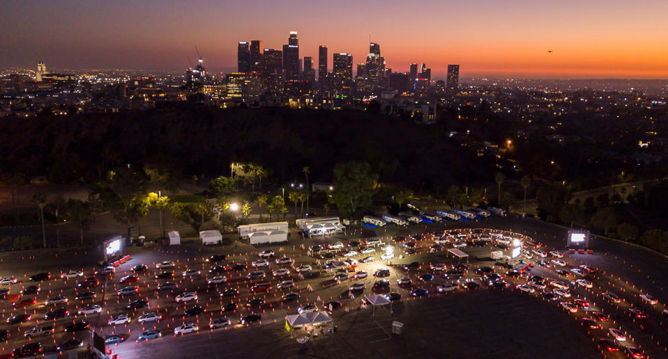 This aerial view shows cars lined up at the Dodger Stadium parking lot for Covid-19 testing with the downtown Los Angeles skyline in the distance.
