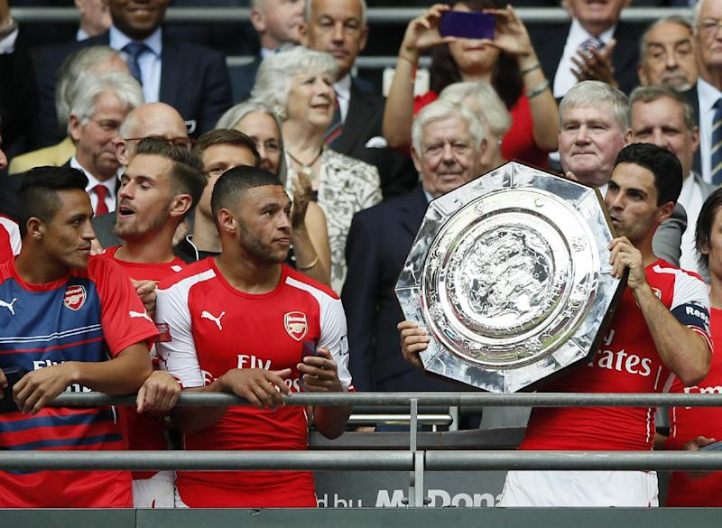 Arsenal's Mikel Arteta kisses the trophy as he goes to hold up the English FA Community Shield after his team defeated Manchester City following the traditional season opening soccer match at Wembley Stadium, London Sunday, Aug. 10, 2014. Arsenal won the game 3-0. (AP Photo/Alastair Grant)