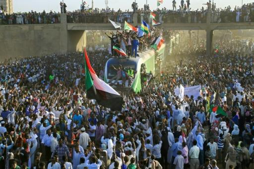 Sudanese protesters cheer as a train bearing them from the capital Khartoum arrives in the town of Atbara, the cradle of the uprising that overthrew Omar al-Bashir