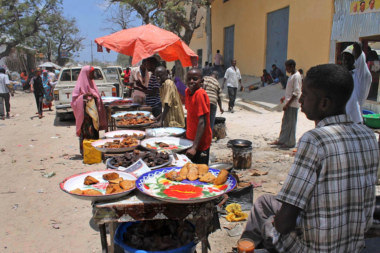 In this photo taken Thursday, March 29, 2012, Somali vendors sell street food at the Hamarweyne market in Mogadishu, Somalia. The seaside capital of Mogadishu is full of life for the first time in 20 years after African Union and Somali troops pushed Islamist militants out of the city last year. (AP Photo/Farah Abdi Warsameh)