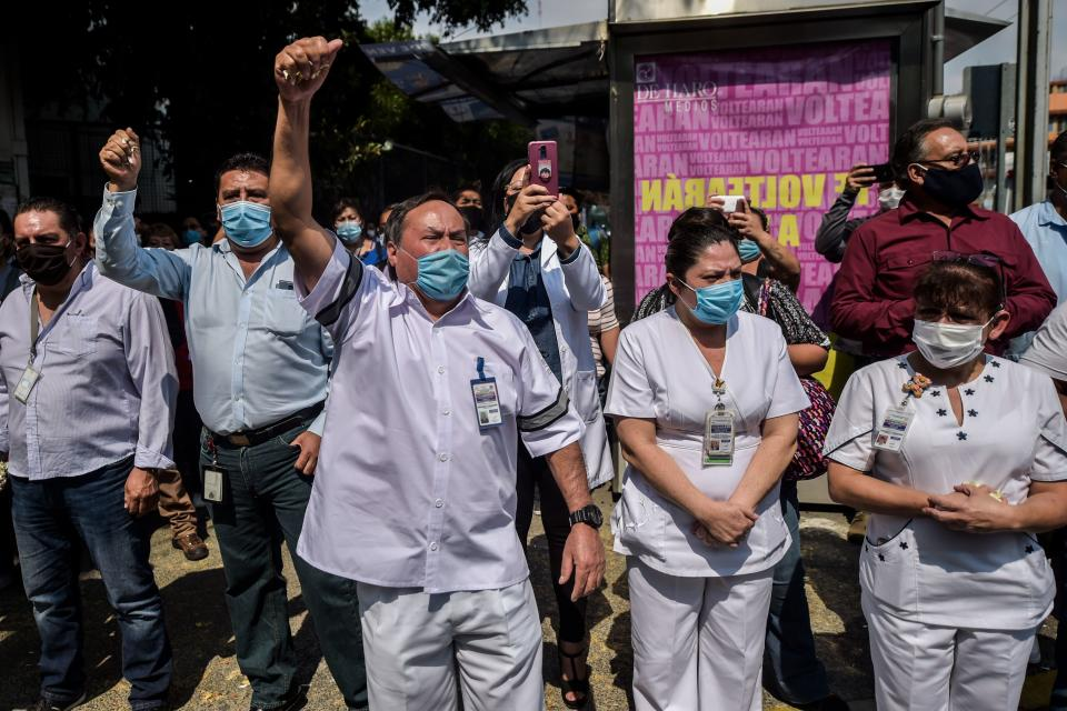 """TOPSHOT - Health workers of """"20 de Noviembre"""" hospital farewell his fellow stretcher-bearer Hugo Lopez Camacho, who died of Covid-19, in Mexico City, on May 18, 2020. - The novel coronavirus has killed more than 30,000 people in Latin America and the Caribbean since the outbreak first emerged in China last December, according to the latest tally from official sources compiled by AFP on Monday. (Photo by PEDRO PARDO / AFP) (Photo by PEDRO PARDO/AFP via Getty Images)"""