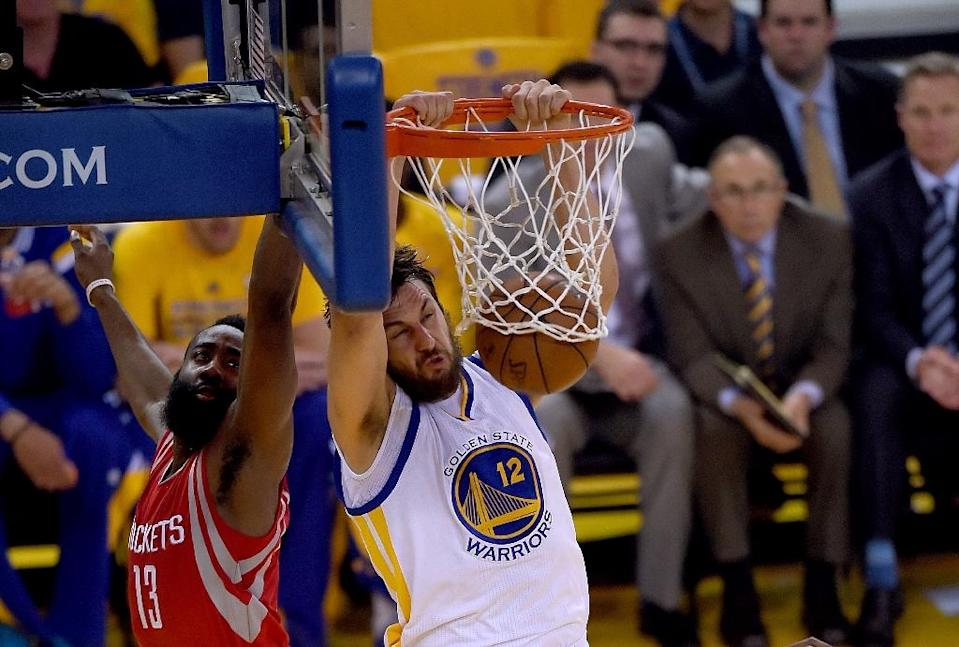 Andrew Bogut (R) of the Golden State Warriors slam dunks against James Harden of the Houston Rockets during the Western Conference Finals of the NBA Playoffs, at ORACLE Arena in Oakland, California, on May 21, 2015 (AFP Photo/Thearon W. Henderson)
