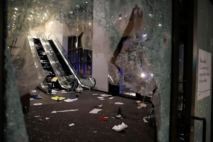Glass is shattered in the Nordstrom store after a riot occurred in the Gold Coast area of the city early in the morning of Monday, Aug. 10, 2020 in Chicago.  Hundreds of people smashed windows, stole from stores and clashed with police in Chicago's Magnificent Mile shopping district and other parts of the city's downtown.