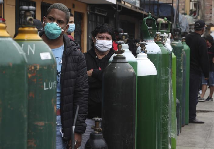 People wearing masks to prevent the spread of the new coronavirus stands in line to refill their empty oxygen cylinders in Callao, Peru, Wednesday 3, 2020. Long neglected hospitals in Peru and other parts of Latin America are reporting shortages of Oxygen as they confront the COVID-19 pandemic. (AP Photo/Martin Mejia)