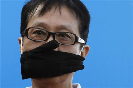 A protester covers his mouth with a glove during a demonstration demanding freedom of speech and press freedom in Hong Kong February 23, 2014. REUTERS/Bobby Yip
