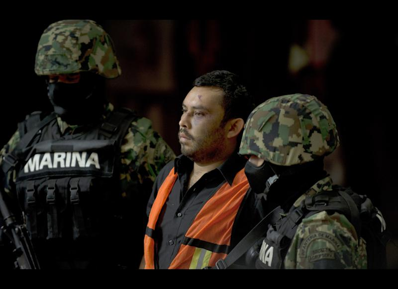 Mexican marines escort Marcos Jesus Hernandez Rodriguez, aka 'El Chilango', alleged leader of assassins and member of the Los Zetas drug cartel, in Veracruz state, during his presentation for the press in Mexico City on May 11, 2012. (YURI CORTEZ/AFP/GettyImages)