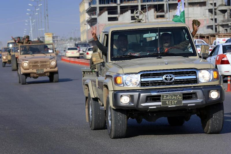 Kurdish peshmerga troops flash the V-sign of victory as they drive through Arbil on October 28, 2014 (AFP Photo/Safin Hamed)