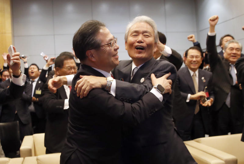 Japan's Economy, Trade and Industry Minister Hiroshige Seko,left, and head of 2025 Japan World Expo committee Sadayuki Sakakibara celebrate after winning the vote at the 164th General Assembly of the Bureau International des Expositions (BIE) in Paris, Friday, Nov. 23, 2018. Japan's Osaka will host the World Expo in 2025, beating out Russia, Azerbaijan for an event that attracts millions. (AP Photo/Christophe Ena)