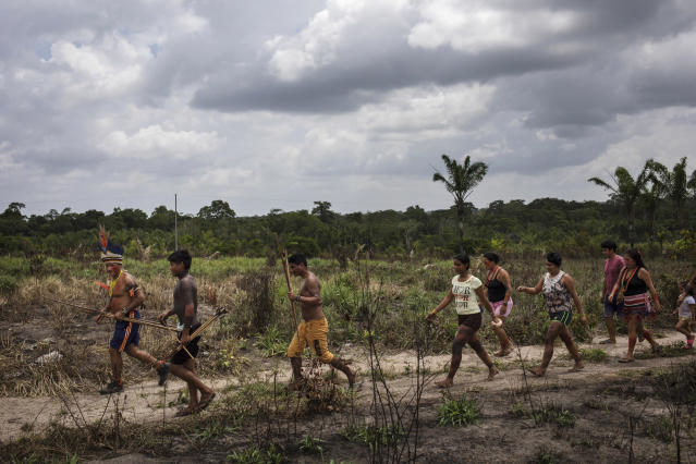 In this Sept. 4, 2019 photo, Cajueiro cheiftain Sergio Muxi Tembe leads villagers to the second day of meetings among the Tembe tribes in the Alto Rio Guama Indigenous Reserve, in Para state, Brazil. Under a thatch-roof shelter in the Amazon rainforest, warriors wielding bows and arrows, elderly chieftains in face paint and nursing mothers gathered to debate a plan that some hope will hold at bay the loggers and other invaders threatening the tribes of the Tembe. (AP Photo/Rodrigo Abd)