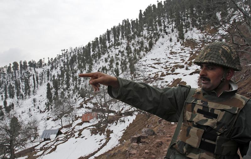 """An Indian army soldier points towards the Pakistan side of the border near the Line of Control (LOC), the line that divides Kashmir between India and Pakistan, in Churunda village, about 150 kilometers (94 miles) northwest of Srinagar, India, Tuesday, Jan. 15, 2013. India's relations with arch rival Pakistan """"cannot be business as usual"""" in the wake of a spate of attacks in Kashmir, Prime Minister Manmohan Singh said Tuesday in a statement that threatens to ratchet up tensions in the wake of the Himalayan violence. A series of tit-for-tat attacks, including the beheading of an Indian soldier, across the LOC that divides the Himalayan region has killed two Pakistani and two Indian soldiers over the past 10 days. (AP Photo/Mukhtar Khan)"""